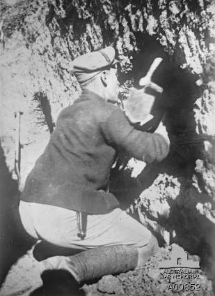 Sergeant Harold Clifton Rodda, 22 Battalion, kneeling on the ground, digging himself a dugout in the side of a trench at Gallipoli, 1915. (Photograph courtesy Australian War Memorial.)