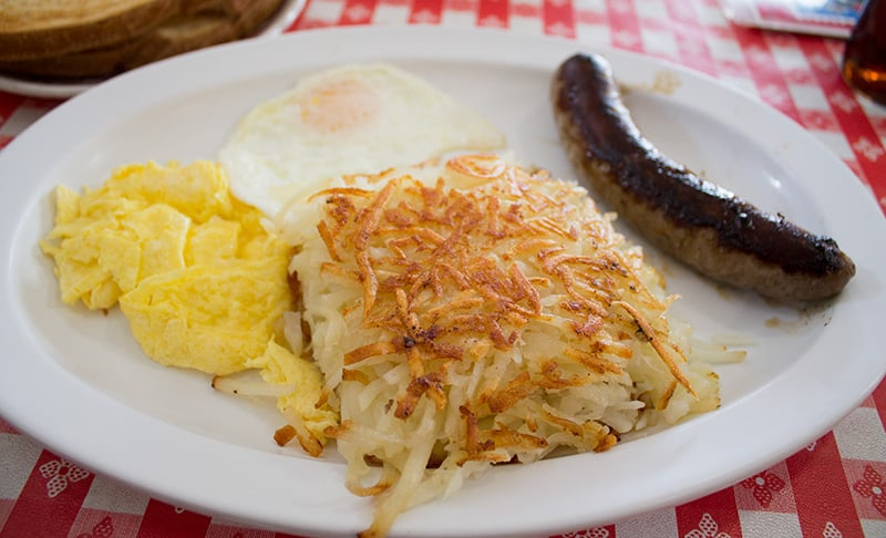 Danish sausage breakfast plate with a fat deck of hash browns and eggs two ways.