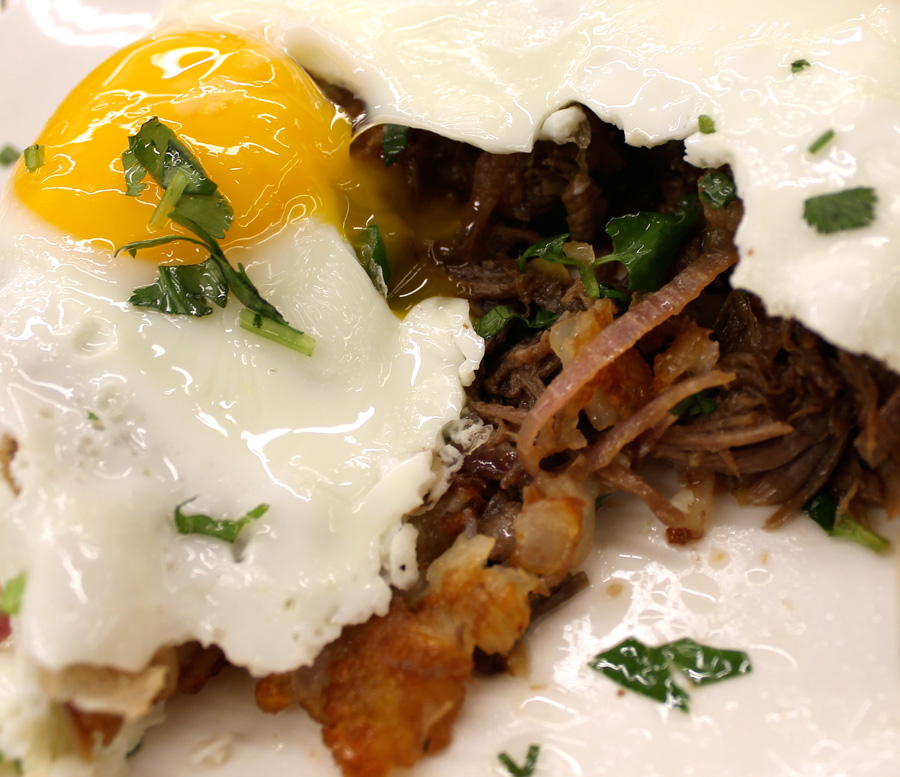 SHAKING BEEF HASH   —   brisket, red + green onion, cilantro, tater tots, sunny eggs, and soy sauce reduction.