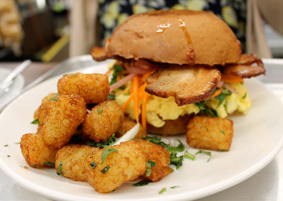 BREAKFAST MI SANDWICH   —   fresh brioche bun, soft scrambled eggs w/green onion + cilantro, house made bacon, 4 cheese blend, pickled red onion, carrots, and brown butter tater tots.
