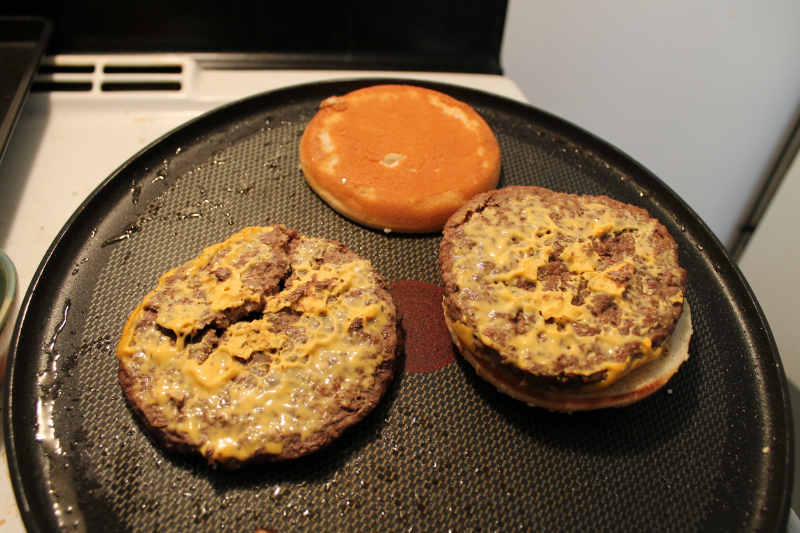 Who doesn't like warm, toasty buns?  Deconstruct your burger as best as you can (sometimes there'll be stickage). Put your burgers and buns on a pan set to low heat.