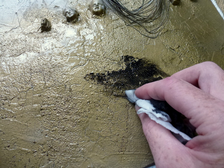 To highlight the texture of the sand and crackle medium apply some heavy black gesso using a moist baby wipe; rub into cracks and depressions and then buff off excess.