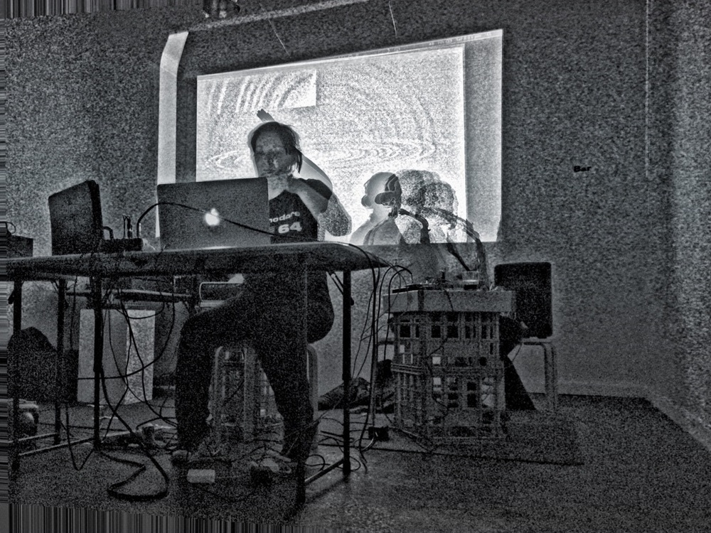 Conduit Arts 2015  Tina Douglas (Laptop, sensor devices synthesizing 3D position data: Nintendo Will controller / Leap Motion controller, electronics, sound reactive video feed). Llloyd Honeybrook (saxophone, electronics).