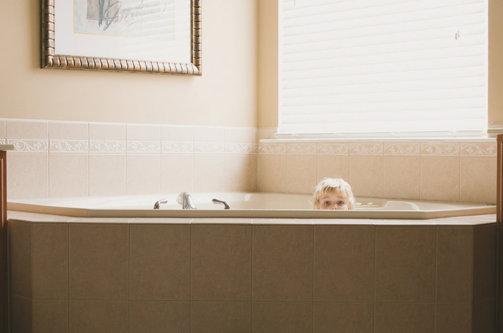 A child peeks out of her bathtub during a Day in the Life photo session in Maryland.
