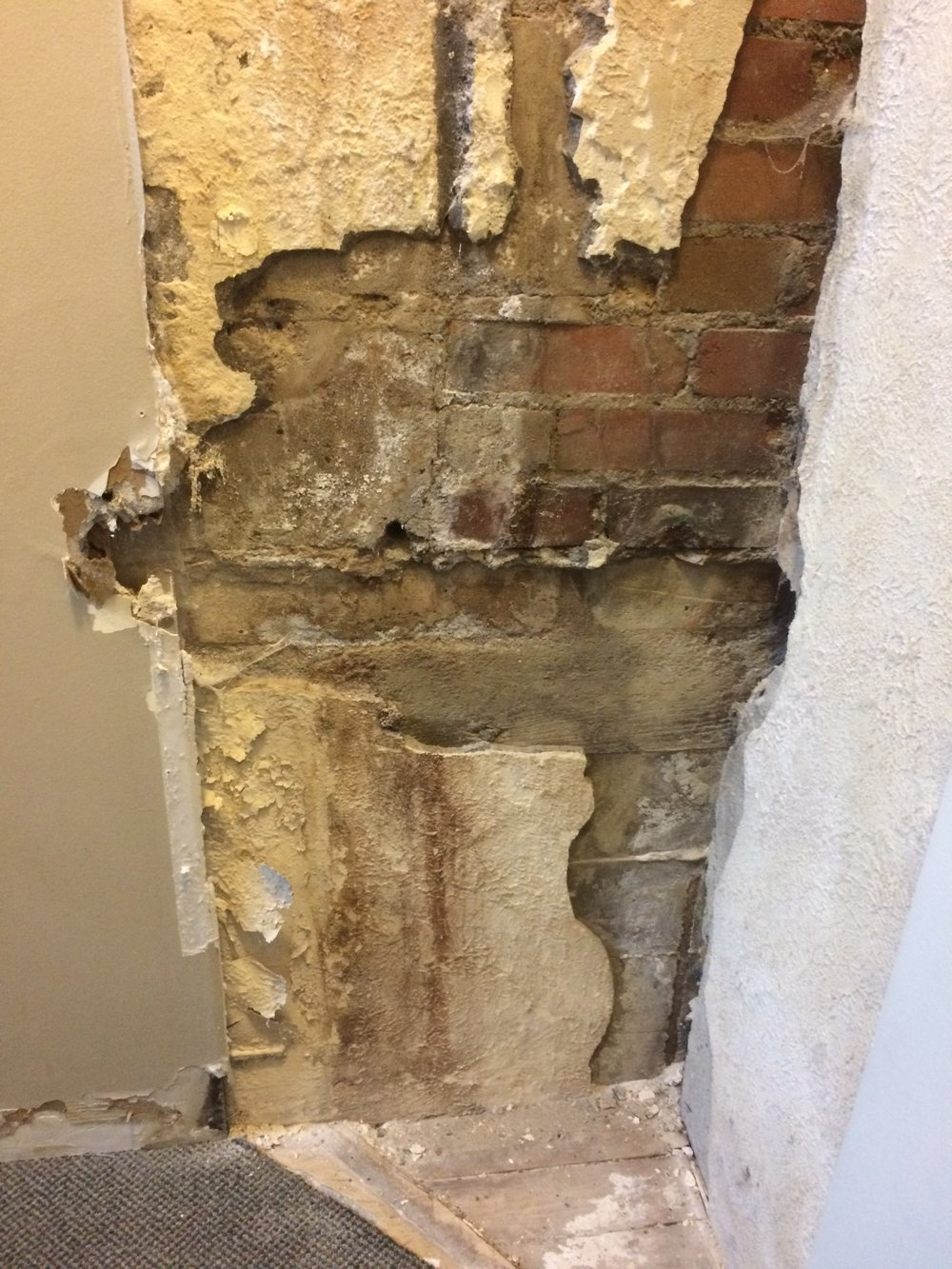 Close up at the bottom of the stairs where seepage was the worst. A panel was installed here so we can continue to open the panel and view the wall condition.