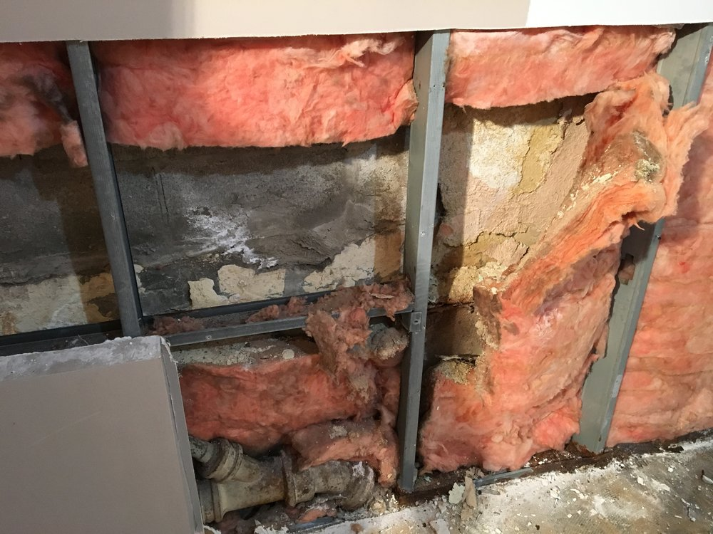 In another location, removing the pink fibreglass insulation reveals the level of damage to the foundation wall itself and old defunct pipes that add to the problem.