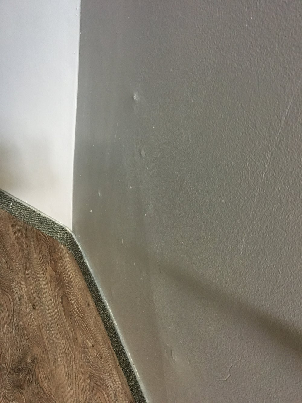 "Multiple points pushing OUT from moisture seepage, here in the front East stairwell, plus evidence the drywall was repaired years ago ... thus this is a longstanding, ongoing issue that will not ""go away"" if we just ignore it."