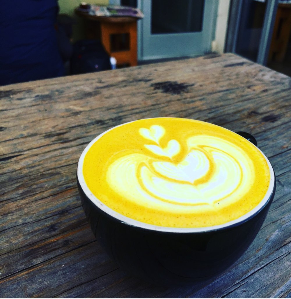 This decadent caffeine-free latte is our riff on a popular anti-inflammatory treat. The glowing turmeric dances with the heat of black pepper, ginger, and sweet almond milk to support your well-being. Our golden lattes contain organic turmeric, ginger, black pepper, cardamom, coconut oil, and honey. We enjoy them most with almond milk, even if you're not vegan!  We've been looking for a caffeine-free, energizing alternative to our espresso based latte. This turmeric based beverage is our delicious option for customers looking for something a little different.