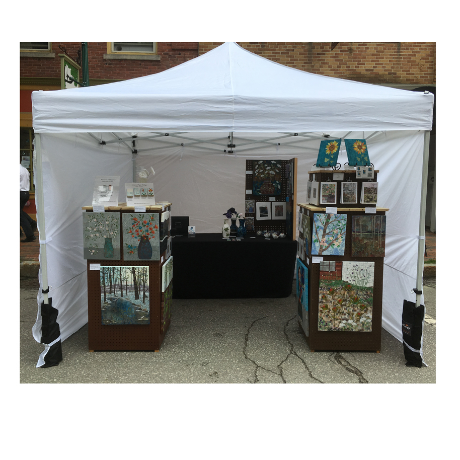 Pinecone and Sparrow Booth Display at the Greater Gardiner River Festival June 17, 2017. Layered paper collage wall art, matted collage art, vases with flowers, ornaments, refrigerator magnets and greeting cards.