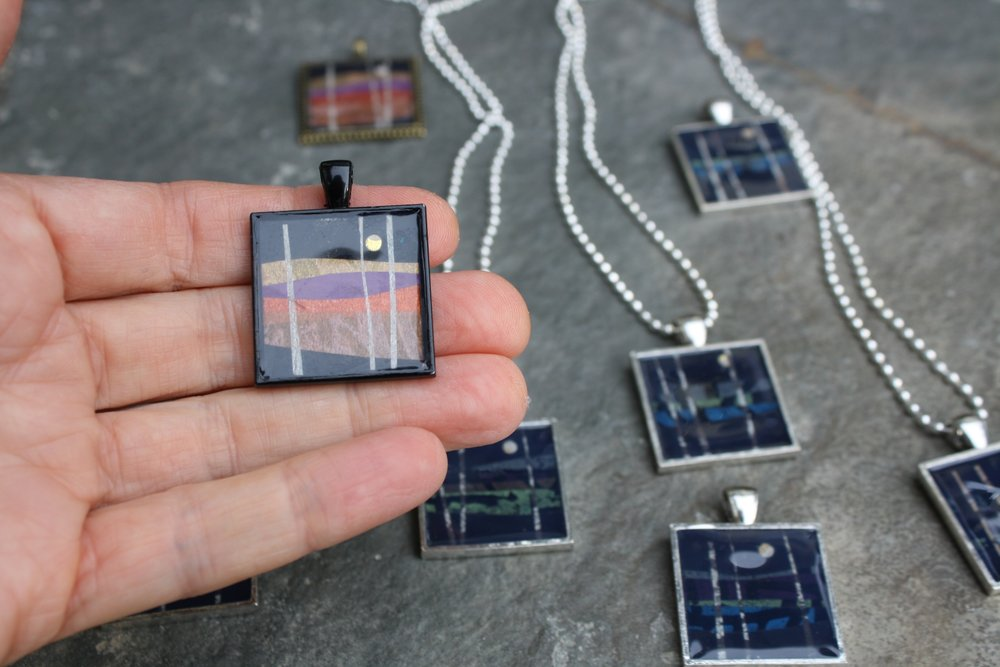 "1"" x 1"" layered paper collage in pendant/bezel trays for necklaces."