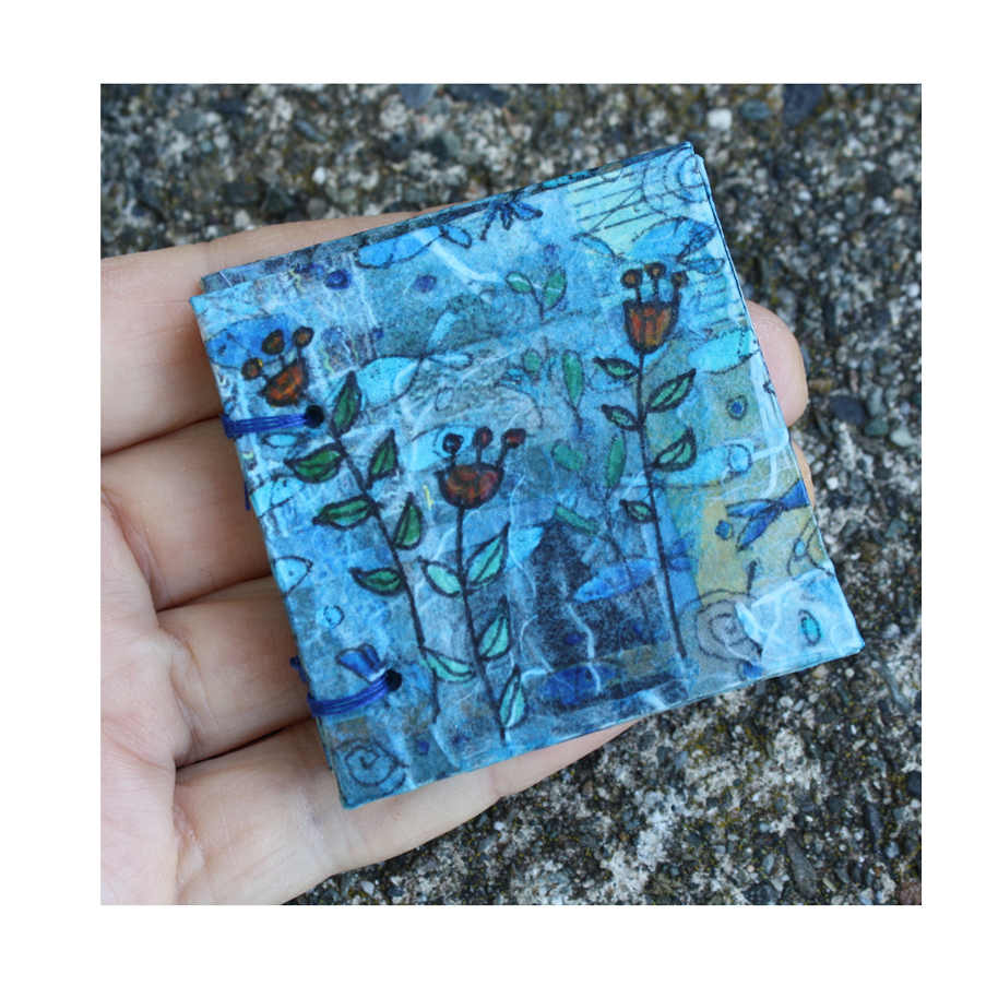 """Fish and Flowers. (2018). Small format collage book. Hand-drawn and painted paper with acrylics and ink on recycled cardboard. 2"""" x 2""""."""