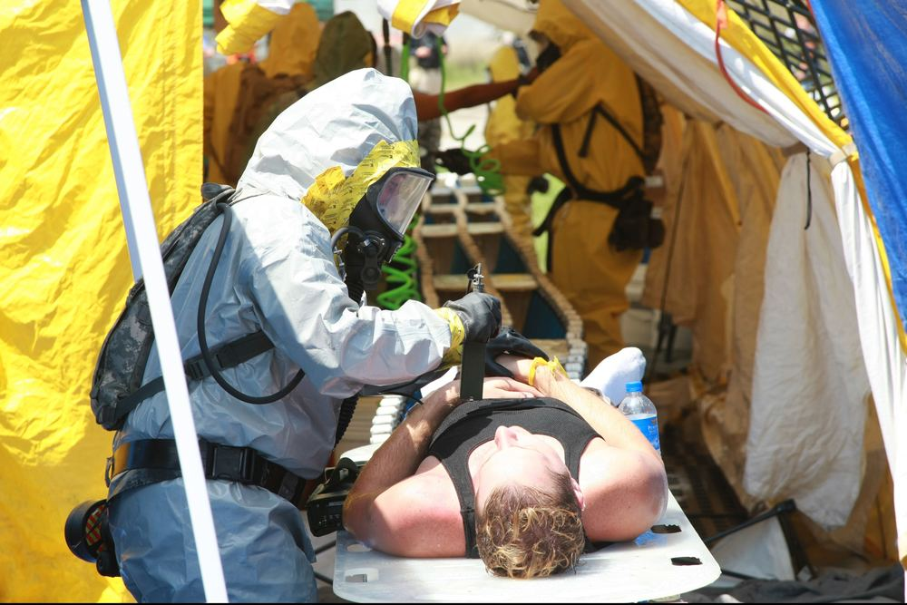 A_U.S._Soldier_attired_in_chemical_suit_measures_radiation_levels_of_a_simulated_nuclear_blast_victim_during_Vibrant_Response_12_at_the_Muscatatuck_Urban_Training_Complex,_Ind.,_Aug_110817-A-TC840-003.jpg