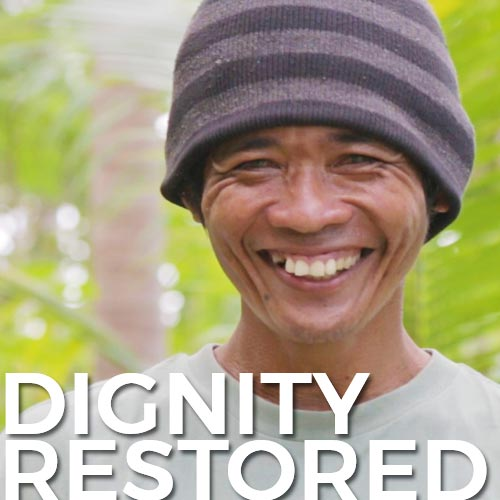 "A Filipino man smiling into the camera with palm trees and coconuts behind him with the words ""dignity restored"" written on the bottom"