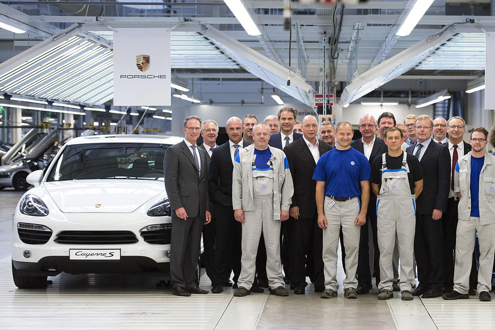 A range of Porsche workshop and managerial staff on the factory floor.