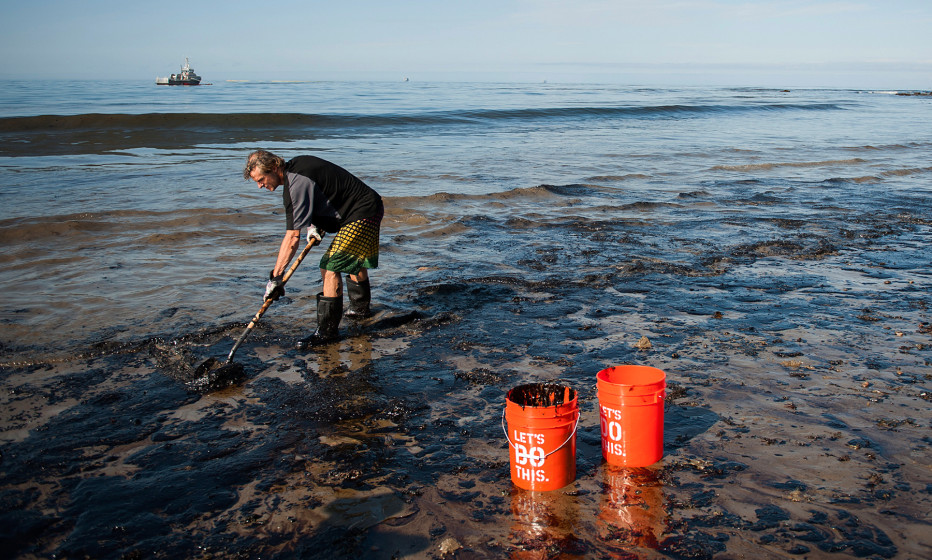A man shovels up oil on a section of beach about a mile east of the Refugio oil spill in California, May 2015.