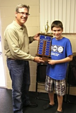 John accepts trophy from last year's winner Larry Storch