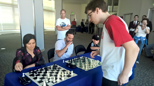 GM Janek-Krzysztof Duda (FIDE 2660) (R) conducting a chess Simul during the CFCC Quick Chess tournament.