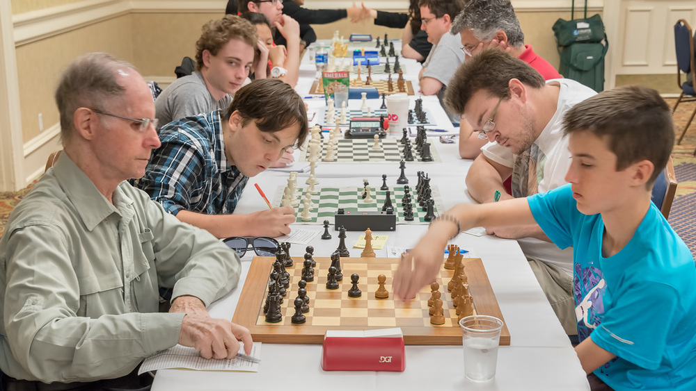 Premier Section Round 4, Board 5: Humberto Cruz (1825) (L) vs Theo Slade (2059) (R); Board 4 Kai Tabor (2051) (L) vs  Florida Chess Association  President William Bowman (1959) (R).