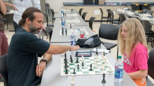 Steven Vigil (L)  Local Chess Coach & USCF Senior TD playing a quick game with Zoe Zelner (R)