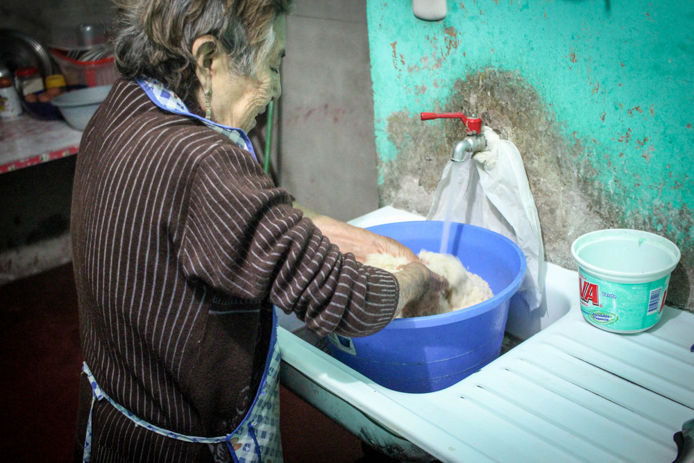 Esperanza washing 4 kilos of rice. She cooks that much rice every day!