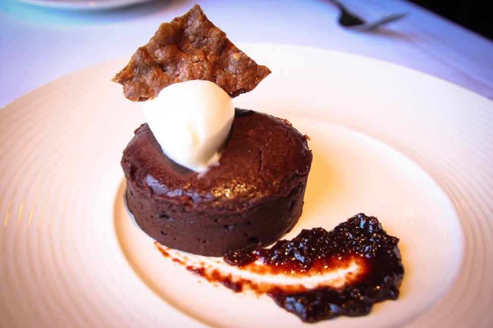 Bittersweet chocolate cake with cherry compôte, crème fraîche sherbet, and pistachio Florentine
