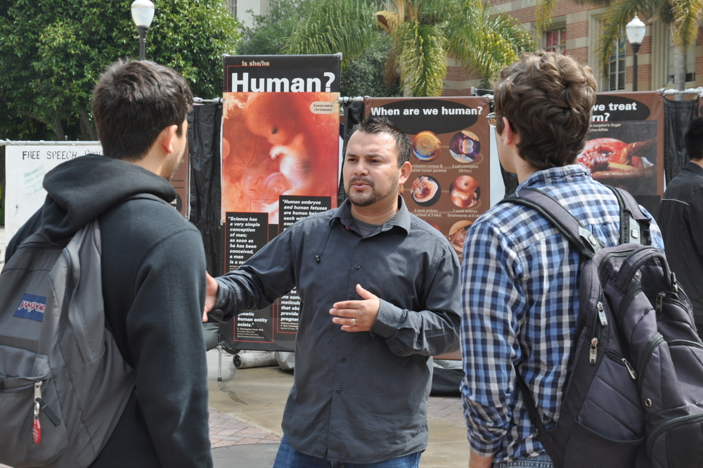 Marcos Espinoza (center), a staff member with Right to Life of Central California, interacts with UCLA students in front of the JFA Exhibit on Bruin Plaza.