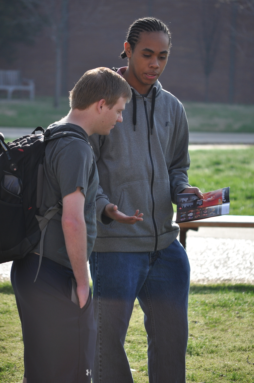 Keawe Bridges (holding brochure) talks with a student at the University of Oklahoma in March 2015.