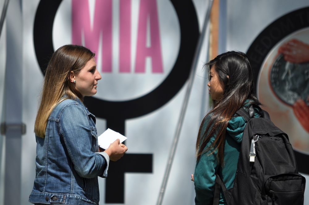 Meredith interacts with a fellow UCLA student in front of the side of the Stop and Think Exhibit focused on feminism and women's rights.