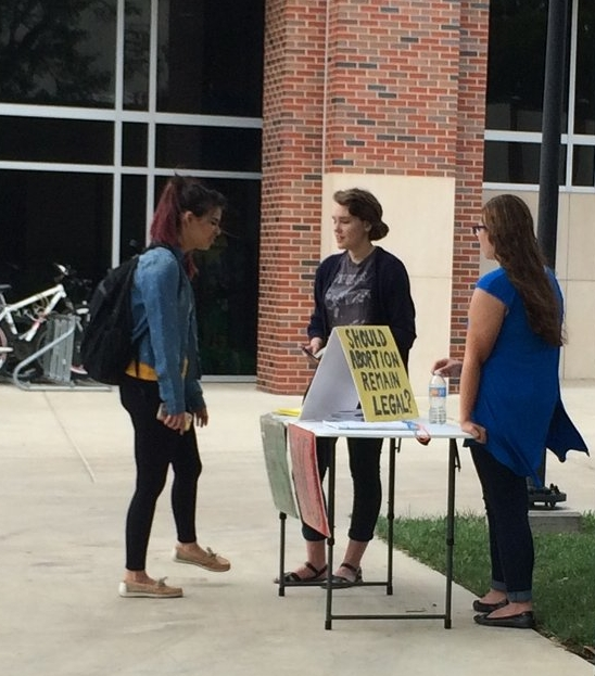JFA's new interns, Grace (middle) and Clare (right), discuss abortion with a pre-med student at WSU about a week after starting their internship with JFA.