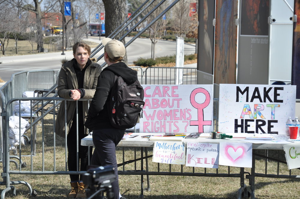 Grace discusses equal rights with a pro-choice student next to the art table at JFA's outreach to the University of Kansas in March 2018.