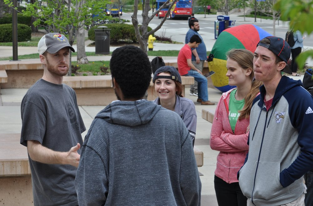 Spencer (left) talks with a University of Kansas (KU) student at a JFA outreach event in April 2016.  Students whom he brought to that outreach event listen in.