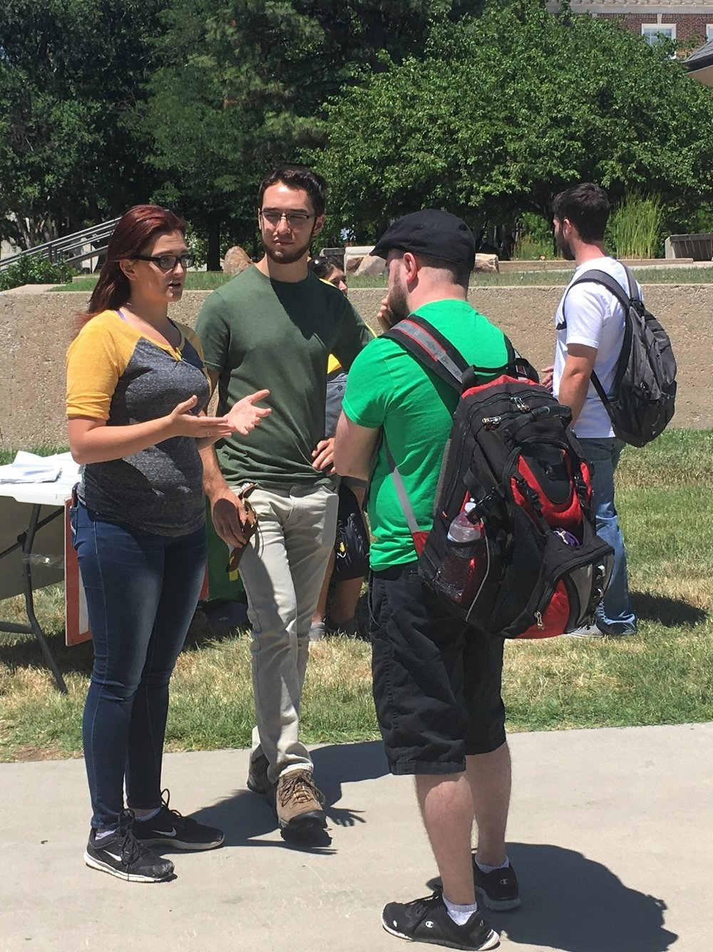 JFA volunteer Ashley (left) talks with a student at JFA's June 2018 outreach at Wichita State University.