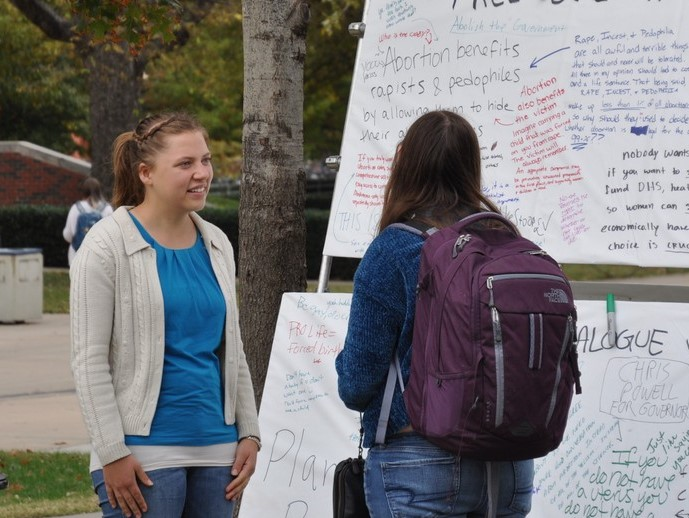 Kaitlyn Donihue (left), talks with a student at JFA's University of Oklahoma (OU) outreach in October 2018.