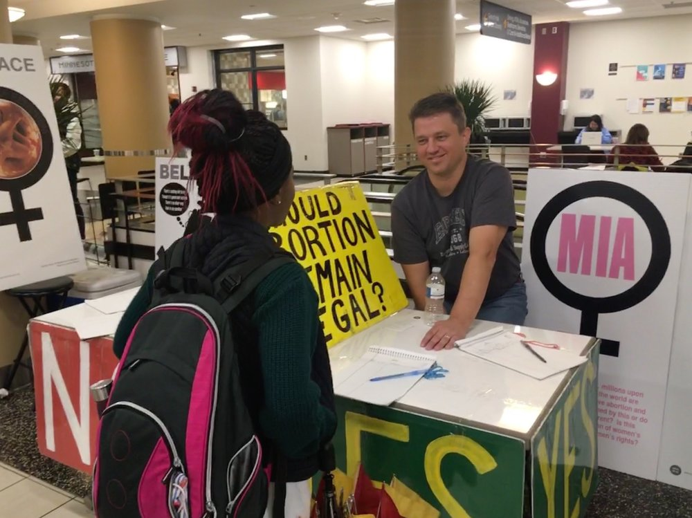 Paul Kulas interacts with a student at UMN. New signs enhance JFA's poll table outreach.