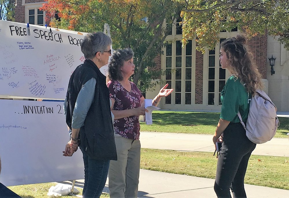 Pauline volunteered again at OU. Here Tammy Cook and Pauline interact with a student near the Free Speech Board.