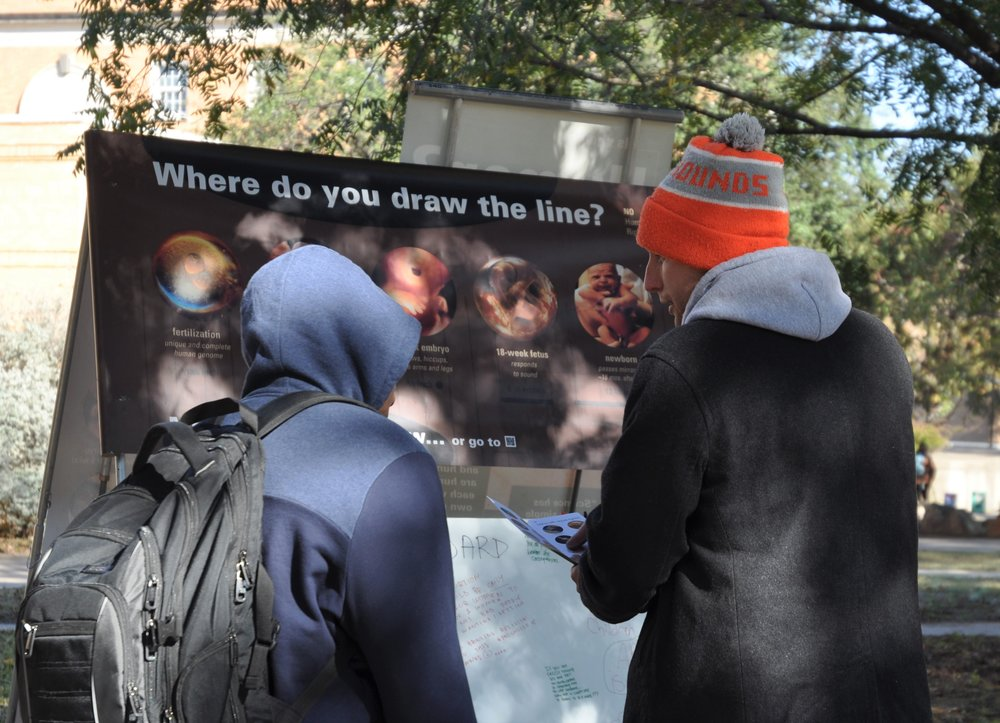 In the conversation Jon Wagner (orange hat) had with Eva, he had the opportunity to share  JFA's brochure  and his reasons for opposing abortion. The same happened with another UNT student pictured above.  (Photo: University of North Texas, November 2018)
