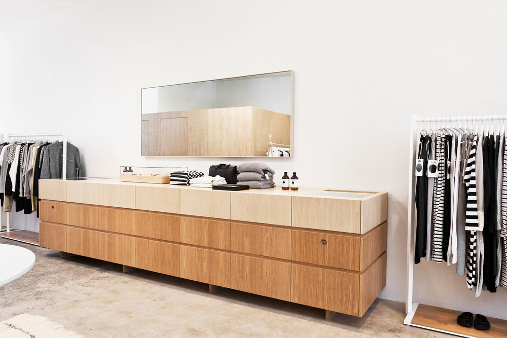 A 16' long storage unit, designed to resemble a credenza, concealed two point-of-sale units and the majority of the store's inventory. The hand crafted, two toned finish of the natural white oak appears to have been created by the natural light from the skylights above.