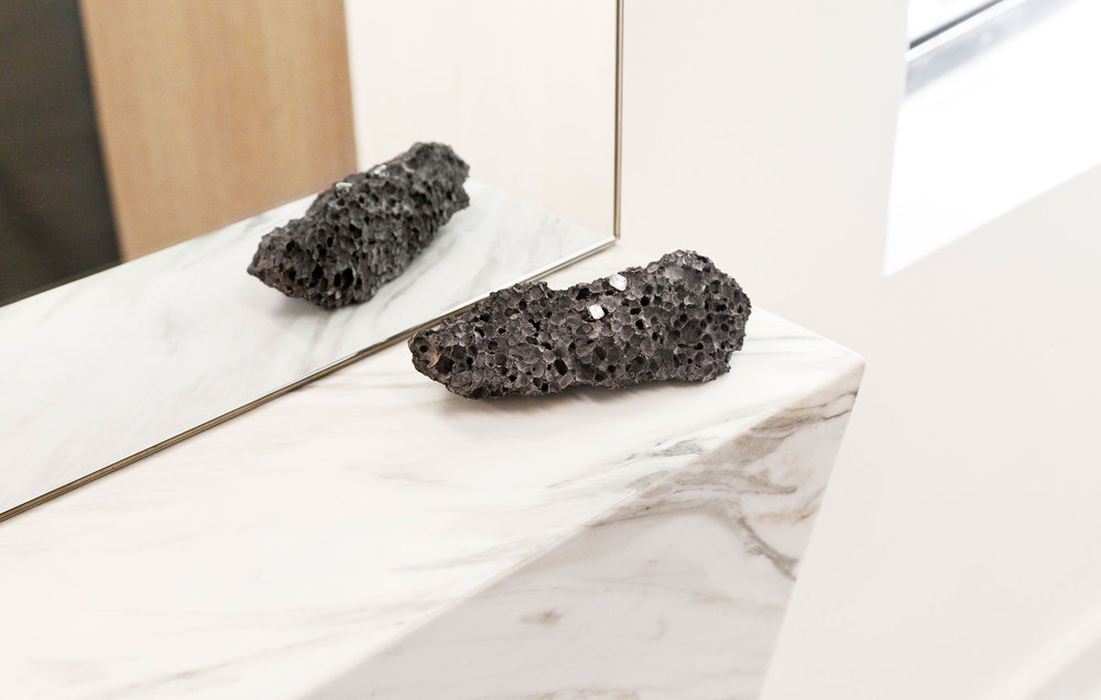 Stud earrings resting on a lava rock at the base of the marble mirror.
