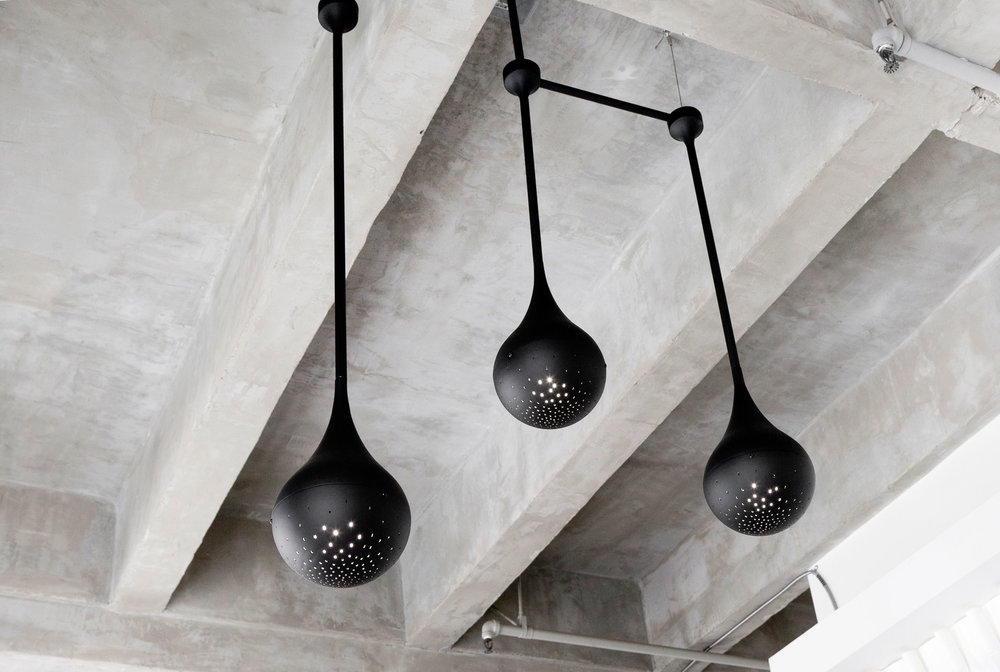 Three Drop Light pendants, designed by Early Work and finished in matte black, are suspended above Grace's desk. Each light is spun by hand in Los Angeles, and features a custom perforated pattern that emits light in a jewel-like manner.  Email to inquire