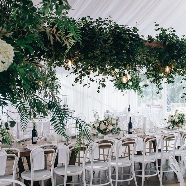 "Ever since @pantone announced 'Greenery' as the colour of the year for 2017 it has fast become the ""it"" colour for wedding styling. It is a vivid shade of green that allows you to bring a natural outdoor setting inside. From bouquets and boutonnieres to table arrangements and hanging installations, this shade will definitely bring freshness to your venue. And we love how @theeventsco_ styled Alex and Geraldine's foliage filled reception! To see more flower styling trends visit the link in our bio… Image @figtreepictures"