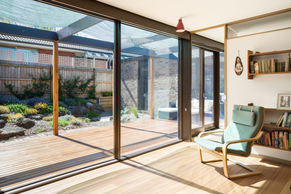Indoor outdoor living space with Hardwood, timer floors and decking and double glazed windows and doors.  Photography by Charlie Kinross