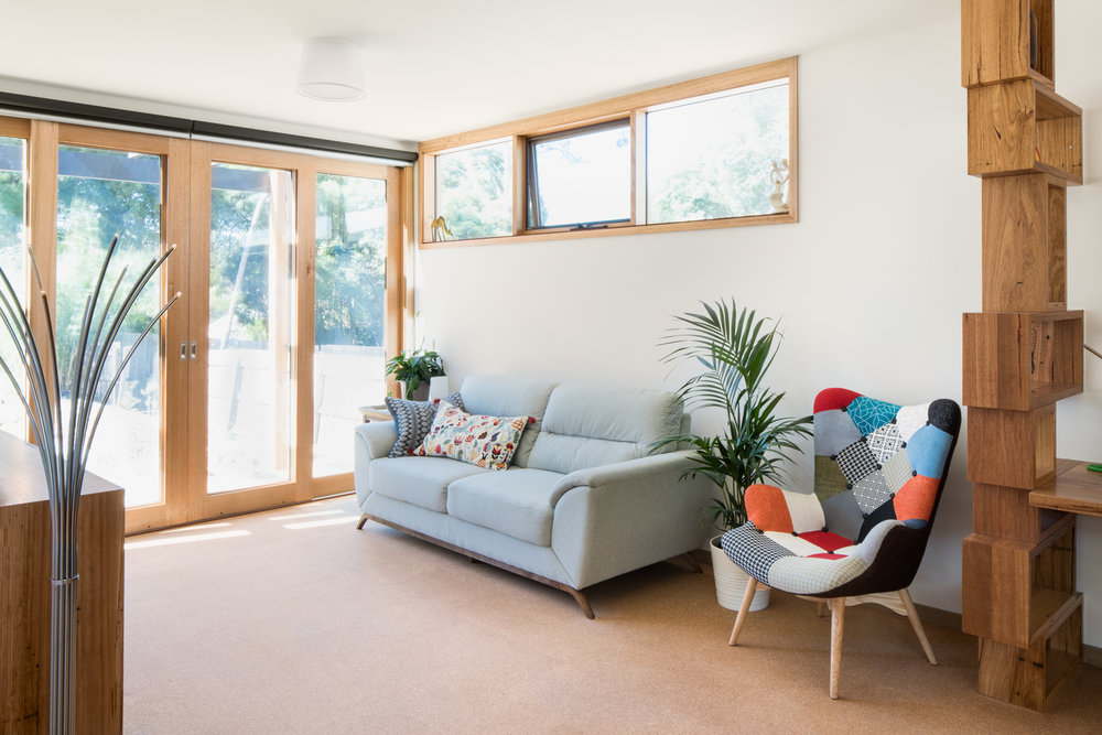 Rear Living Room with recycled hardwood shelving, and Australian Hardwood double glazed windows and doors.  Photography by Charlie Kinross