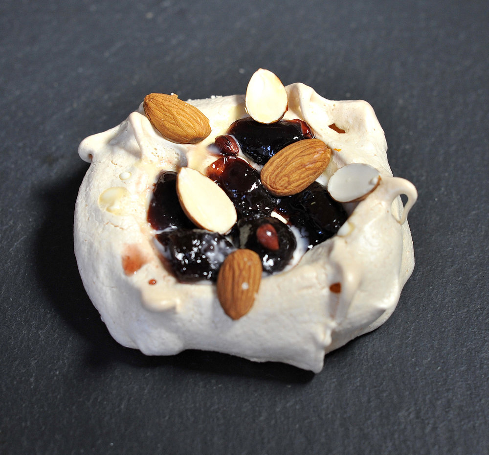 Meringue topped with black cherry & black pepper compote, almonds and cream © Photography by Emmerline Smy