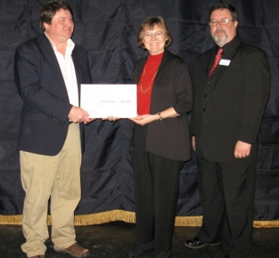 Playwright W. Jeff Bishop accepting the commission from Caroline Abbey and Dave Dorrell.