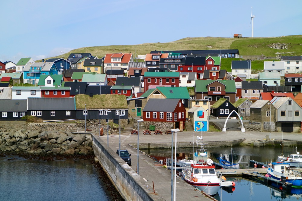 As soon as the ferry M/F Ternan approaches the harbor, you can spot the red brown house with the white window frames, close to the gate made out of whale-jawbone. That's where you will meet Tjóðhild, Anna Malan and Barbara.
