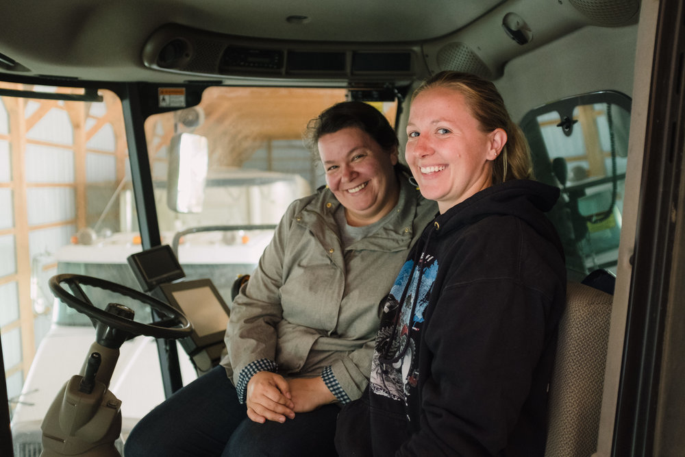 Jess (left) and Rita, sitting in a combine harvester (a machine that combines reaping, threshing, and winnowing into one process). These vehicles are BIG - you have to climb a ladder to get to the driver's seat.