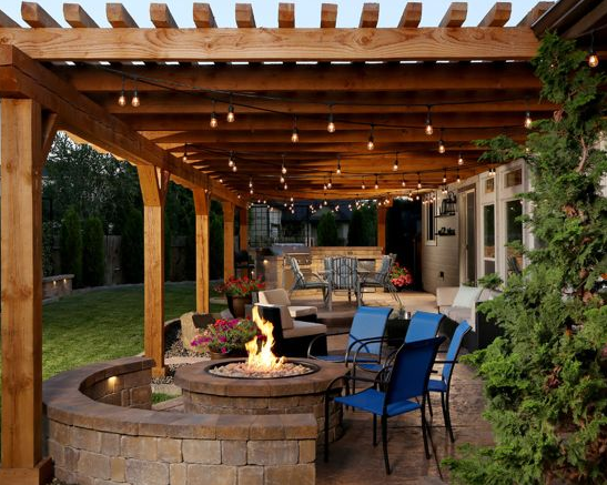 Rustic - Mid-sized rustic backyard stamped concrete patio kitchen idea in Boise with a pergola. Elegant yet  comfy.