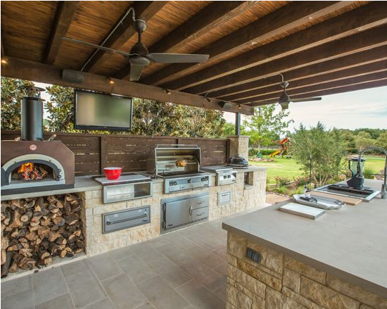 Bon Vivant - This gourmet kitchen includes wood burning pizza oven, grill, side burner, egg smoker, sink, refrigerator, trash chute, serving station and more!