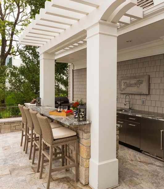 Indulge - This outdoor kitchen/bar provides everything you need to entertain your guests outdoors. The stunning stainless steel cabinets along the wall house a sink, refrigerator and plenty of storage.