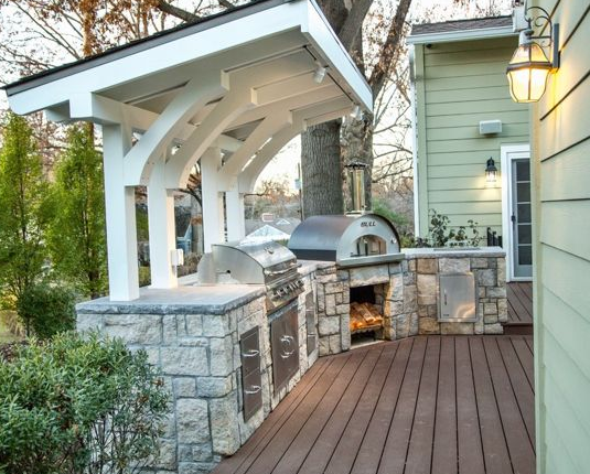 Traditional - Outdoor kitchen deck - Mid-sized traditional backyard outdoor kitchen deck idea in Kansas City with a pergola.